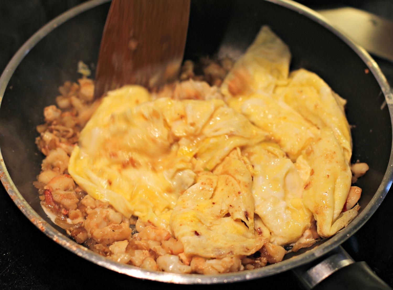Jetzt vermengst du die 3/4 garen Omelettes in der heißen Pfanne mit den angebratenen Krabben und der Schalotten-Ingwer-Knoblauch Mischung.