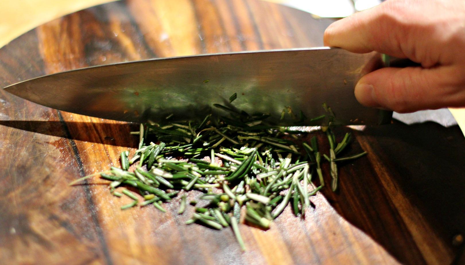 Die frischen Rosmarinnadeln mit einem scharfen Messer feinhacken.