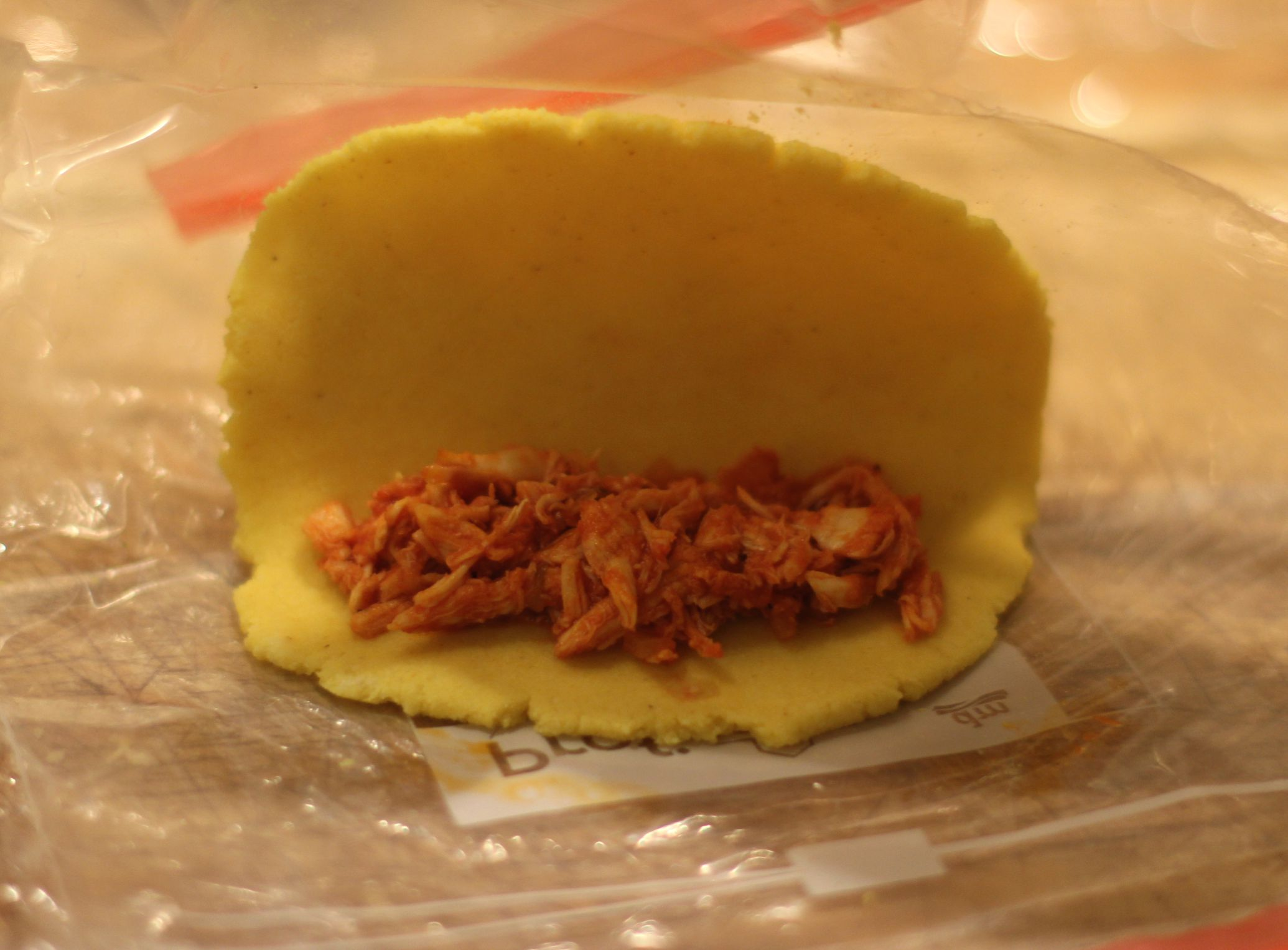 Step 5: Den Gefrierbeutel anheben um den Teig überzuklappen, damit du die Empanada gleich schließen kannst.