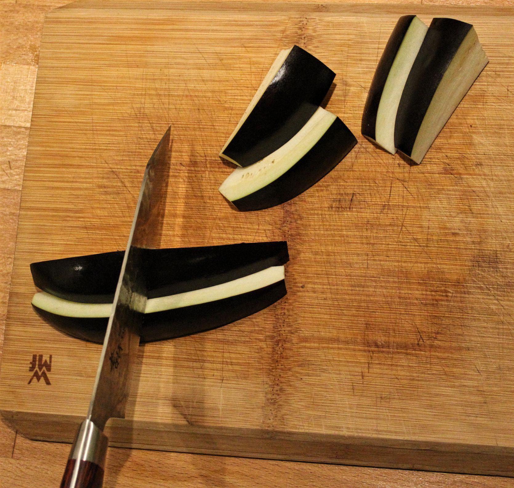 Im zweiten Schritt, werden die Auberginenstücke halbiert.