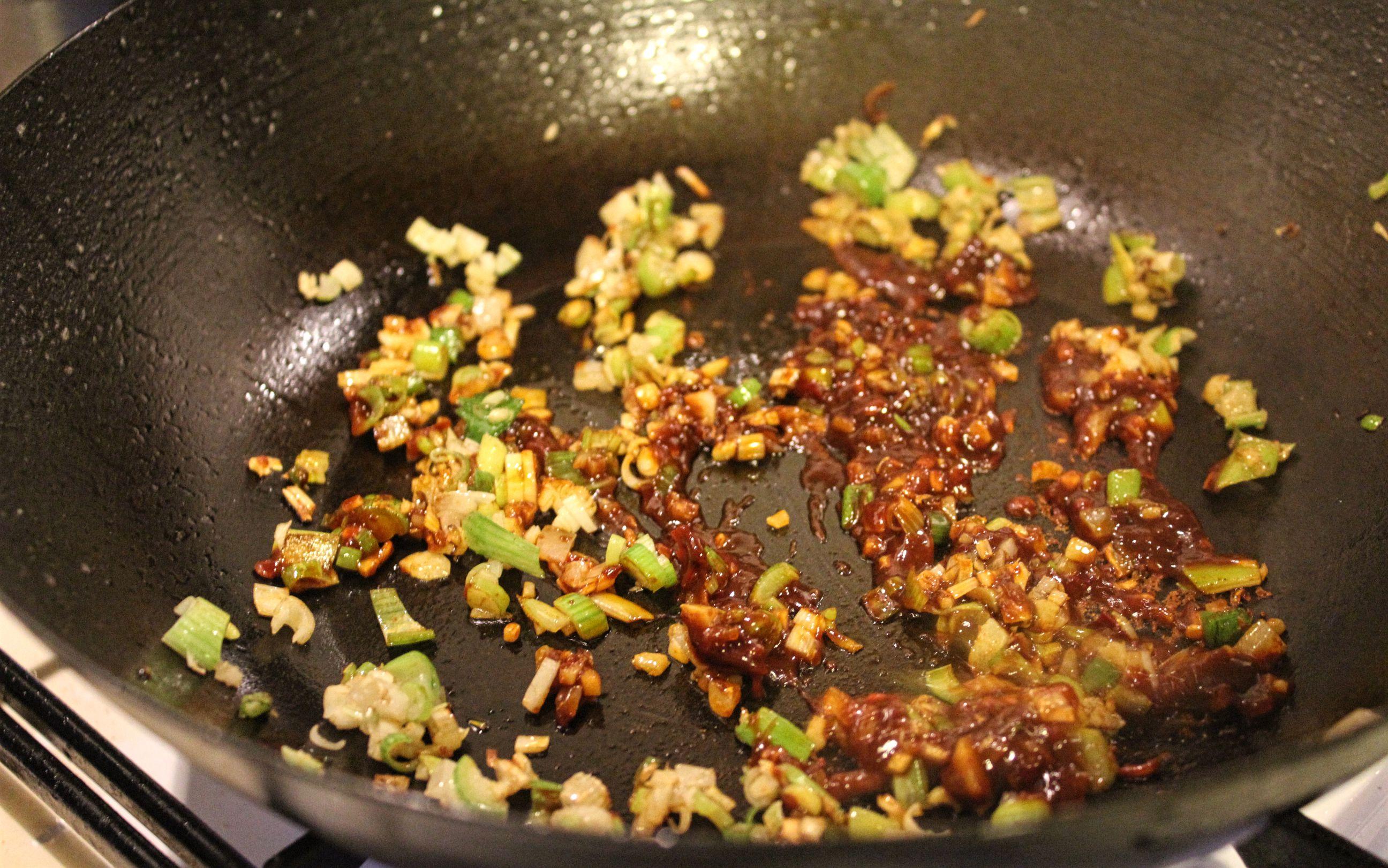 Die Doubanjiang Paste kommt in die Pfanne zu Lauchzwiebeln und Ingwer und wird mitangebraten.
